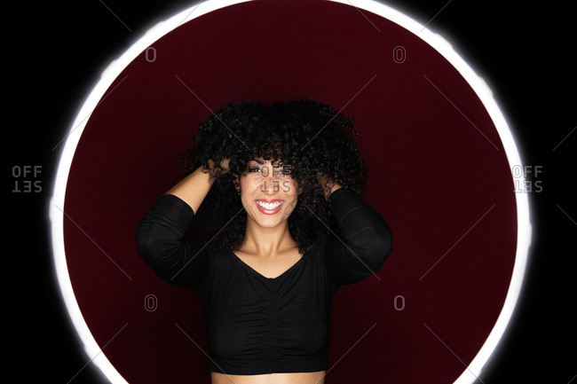 Cheerful African American woman with curly hair standing in a light circle frame looking at camera in studio