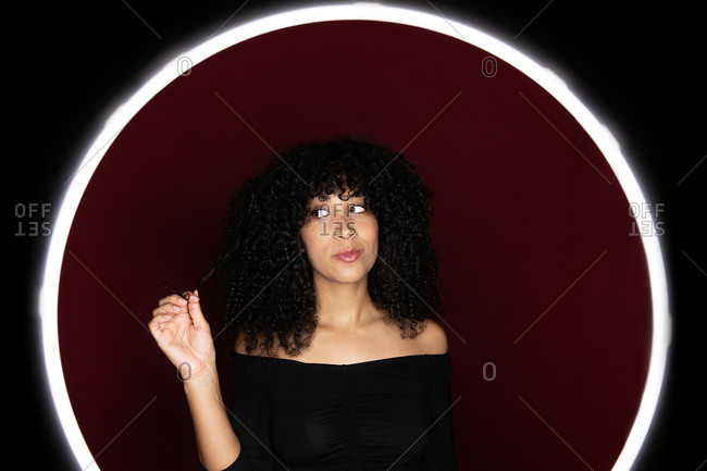 Thoughtful African American woman with curly hair standing in a light circle frame looking away in studio