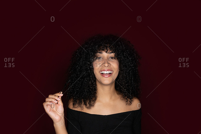 Cheerful African American woman with curly hair standing in a red background looking at camera in studio