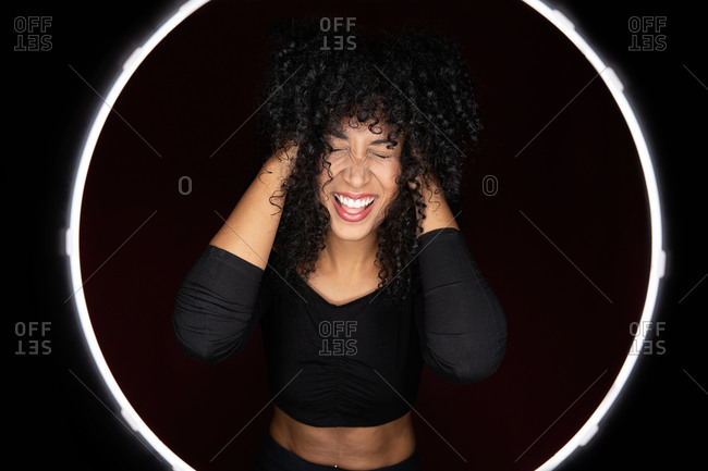 Cheerful excited African American woman with curly hair standing in a light circle frame with eyes closed in studio