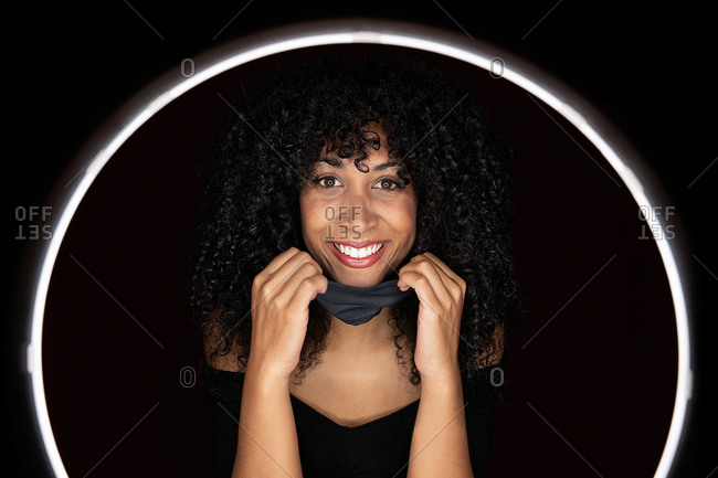Happy African American woman with curly hair putting on a face medical mask against coronavirus standing in a light circle frame looking at camera in studio on black background