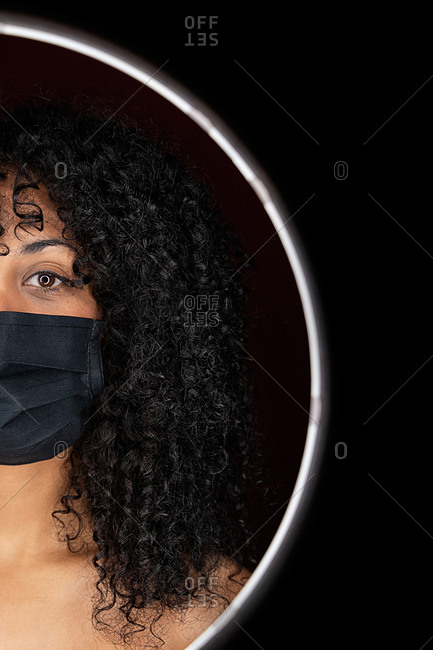 Thoughtful African American woman with curly hair wearing face medical mask against coronavirus standing in a light circle frame looking at camera in studio on black background