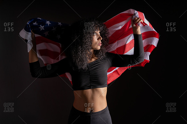 Black woman with curly hair wrapped on the USA flag representing black lives matter activism movement looking away
