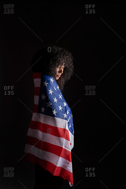 Side view of a black woman with curly hair wrapped on the USA flag representing black lives matter activism movement looking down