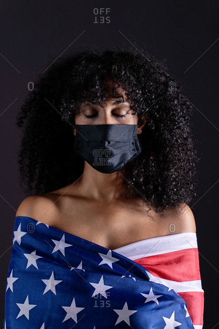 Black woman with curly hair wearing a face medical mask for coronavirus pandemic while standing wrapped on a USA flag representing black lives matter activism movement with eyes closed