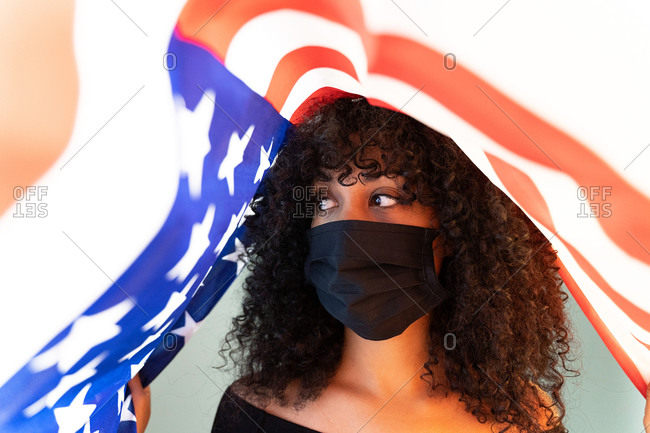 Black woman with curly hair wearing a face medical mask for coronavirus pandemic while standing inside a USA flag representing black lives matter activism movement looking away