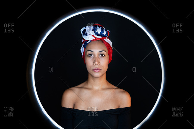 Portrait of a thoughtful black female framed on a led ring wearing proudly the United States of America colors as a head wrap looking at camera