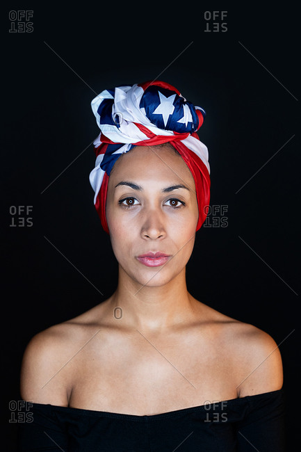 Portrait of a thoughtful black female wearing proudly the United States of America colors as a head wrap looking at camera on black background