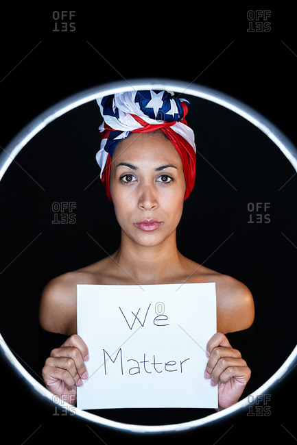 Portrait of a black female framed on a led ring wearing proudly the United States of America colors as a head wrap while holding a whiteboard with the peaceful message black lives matter looking at camera