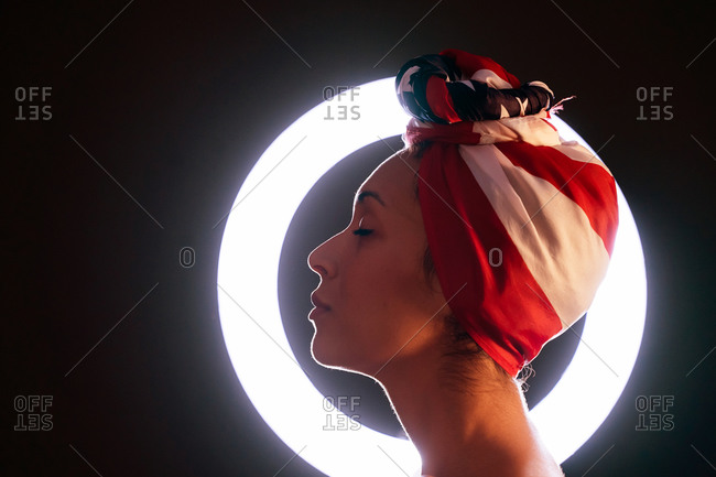 Side view of thoughtful black female standing in front of a led ring light wearing proudly the United States of America colors as a head wrap with eyes closed