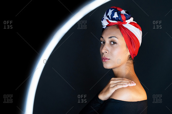Side view of thoughtful black female standing in front of a led ring light wearing proudly the United States of America colors as a head wrap looking at camera