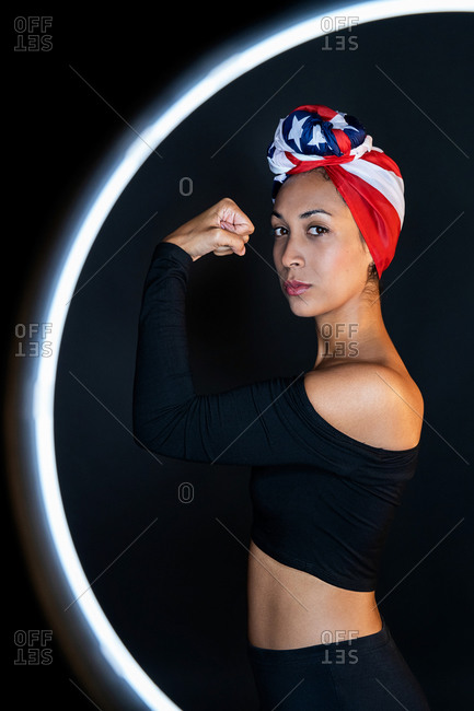 Side view of thoughtful and powerful black female standing in front of a led ring light wearing proudly the United States of America colors as a head wrap while showing arm muscle and strength