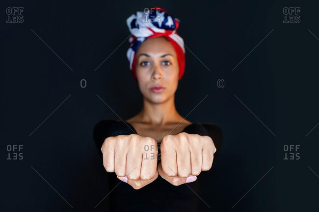 Portrait of a thoughtful black female wearing proudly the United States of America colors as a head wrap and showing fist towards the camera on black background
