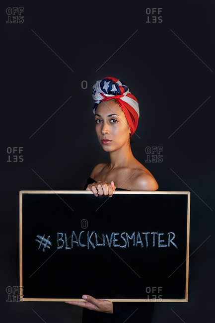 Sad thoughtful black female proudly wearing the United States of America flag as a head wrap while holding a blackboard with the activist message black lives matter looking at camera