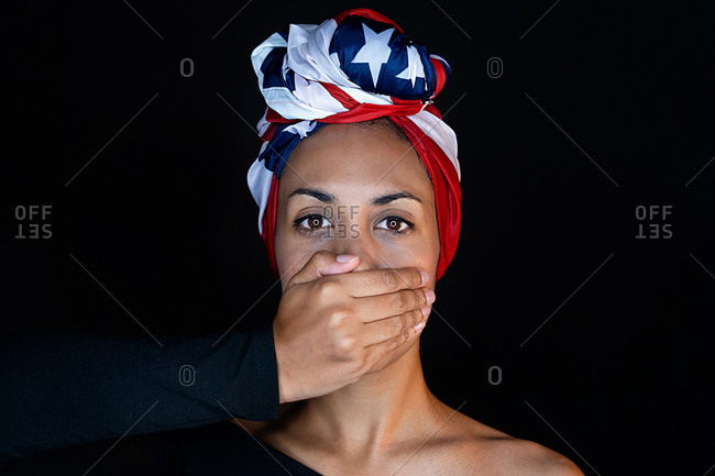 Portrait of scared black female wearing the United States of America colors as a head wrap while having her mouth covered with hands on black background