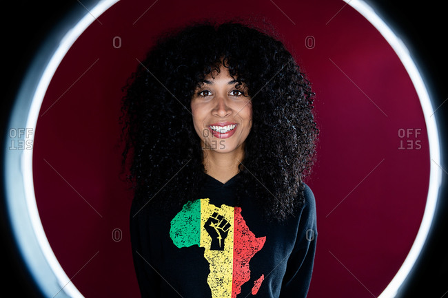 Cheerful young African woman standing in a light ring frame wearing the symbol of Africa continent with a clenched fist in her clothes looking at camera