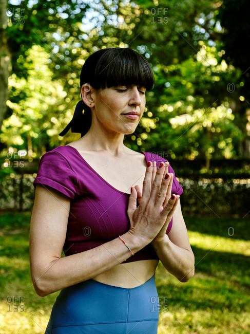 Side view of tranquil woman practicing yoga in Tadasana while standing with closed eyes and Namaste hands in park