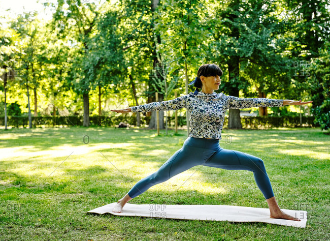 Flexible female in sportswear standing barefoot on mat in park and practicing yoga in Warrior pose while relaxing and looking away