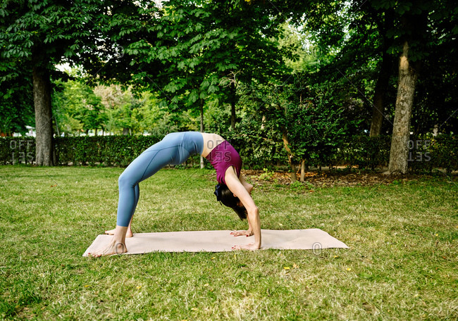 Side view of calm female in sportswear doing yoga in Wheel pose on mat while standing barefoot in park in summer