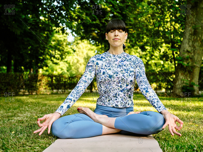 Concentrated female in sportswear sitting on mat in Padmasana with mudra gesture and practicing yoga in park with eyes closed