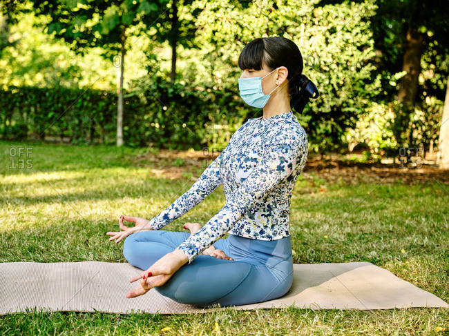 Side view of concentrated female in sportswear and medical mask sitting on mat in Padmasana with mudra gesture and practicing yoga during coronavirus in park with eyes closed
