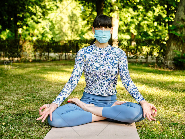 Concentrated female in sportswear and medical mask sitting on mat in Padmasana with mudra gesture and practicing yoga during coronavirus in park