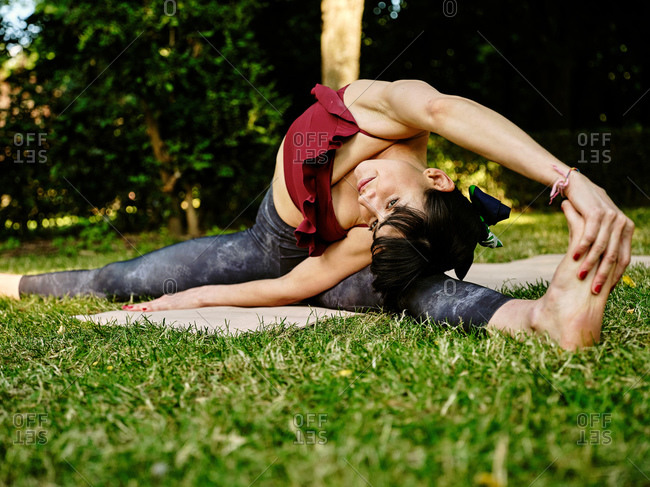 Young slim female in sportswear practicing Parivrtta Upavistha Konasana yoga asana on green grass in summer park