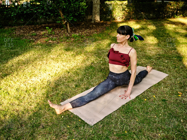 Full body of flexible female yoga trainer performing splits or Monkey pose during yoga session on green grass in summer park