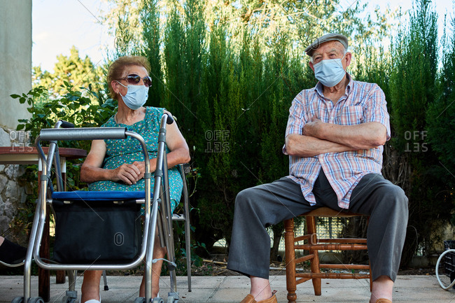 Elderly man and women in protective masks with wheel walker gathering in yard of stone house and talking in summer day