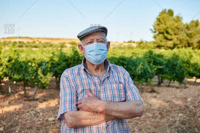 Elderly male in protective mask and casual shirt with cap looking at camera while standing against trees plantation in summer day in countryside