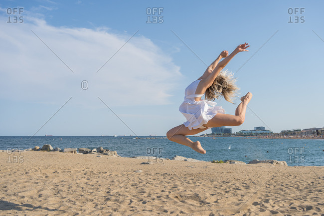 Full length side view of unrecognizable barefoot female dancer in white dress jumping up while performing dynamic dance moves with arms raised on sandy beach