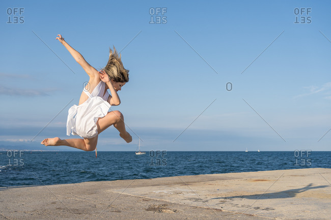 Full body of energetic young female dancer in white dress jumping high against blue sky while dancing on sea embankment