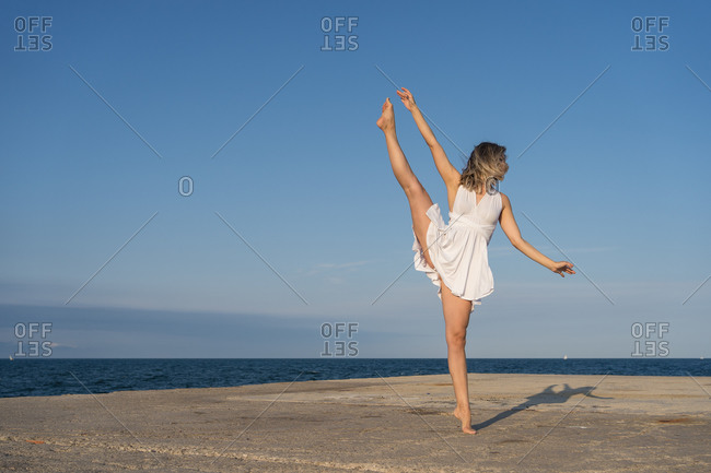 Full body barefoot female dancer in white dress standing on tiptoe and stretching leg while practicing ballet movements on sunny seaside
