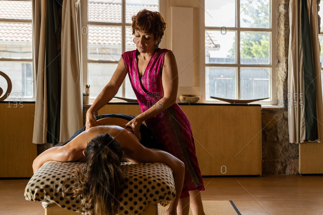 Professional female therapist doing ayurvedic massage with essential oil on back of to relaxed woman in spa salon