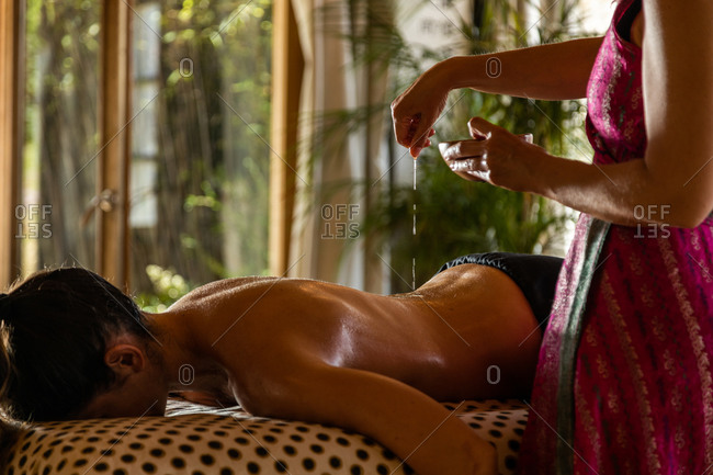 Cropped unrecognizable female therapist with bowl pouring oil on back of unrecognizable customer during ayurvedic healing procedure in salon