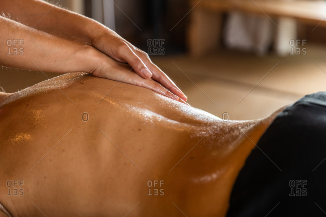 Side view of crop anonymous master performing ayurvedic massage with aromatic oil on back of relaxed customer in modern salon