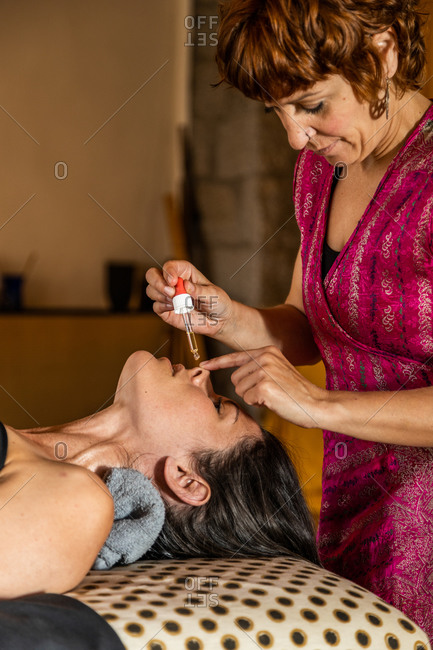Side view of female master with dropper applying essential oil into nose of client during ayurvedic healing procedure