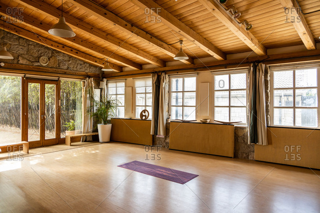 Yoga mat placed on wooden floor inside spacious pavilion decorated in oriental style located in tropical country