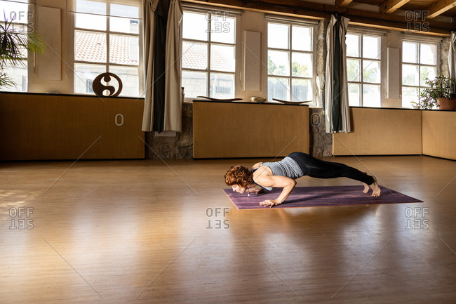 Full body side view of focused female in sportswear doing Chaturanga Dandasana or Four Limbed Staff pose while practicing Shakti yoga alone in spacious studio