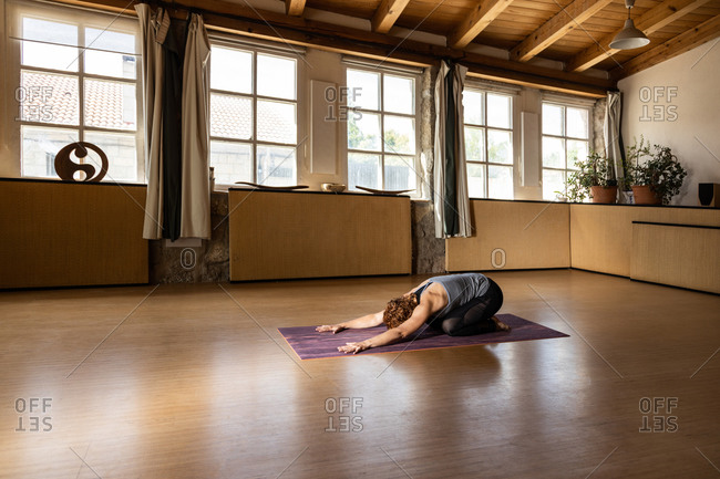 Full body side view of unrecognizable female practicing Shakti yoga and performing Balasana or Child pose in spacious studio