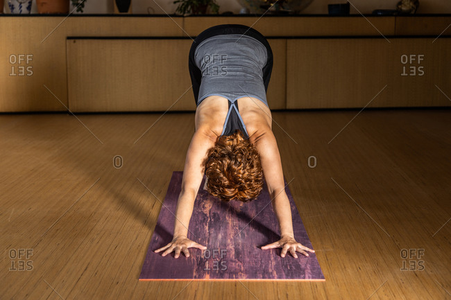 Unrecognizable female in sportswear standing in Downward Facing Dog pose while practicing yoga in studio with wooden floor