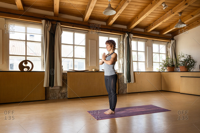 Full body side view of female standing in Mountain pose with namaste hands while practicing Shakti yoga in spacious studio