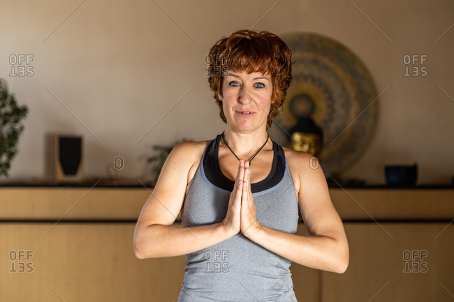 Female standing in Mountain pose with namaste hands practicing Shakti yoga in spacious studio looking at camera