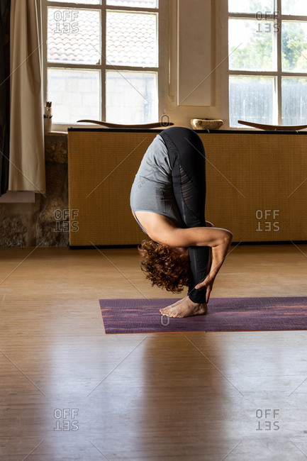 Full body side view of unrecognizable female in sportswear performing Standing Forward Bend pose during Shakti yoga session in light studio with wooden interior