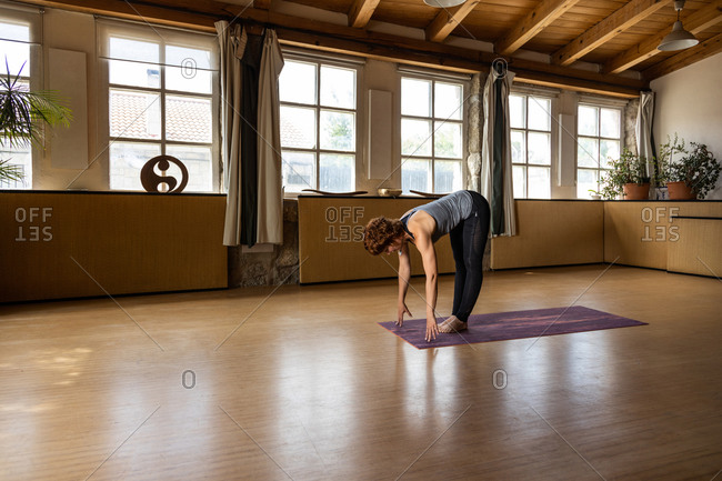 Full body side view of focused female in sportswear standing in Ardha Uttanasana pose during Shakti yoga practice in spacious room with wooden interior