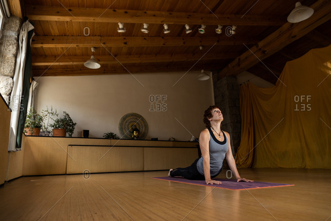 Full body side view of concentrated female in sportswear practicing Shakti yoga alone doing cobra pose in spacious studio