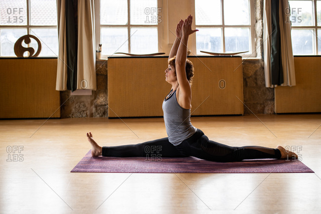 Full body of focused female yogi in sportswear performing monkey pose during Shakti yoga practice in spacious room with wooden interior looking away