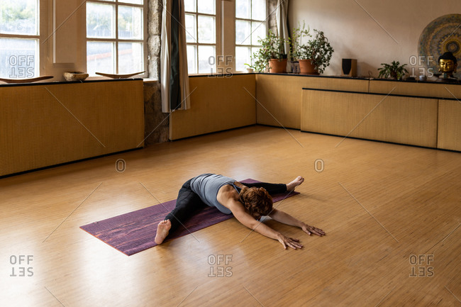 Full body of focused female yogi in sportswear performing Seated Wide Legged Forward Bend during Shakti yoga practice in spacious room with wooden interior