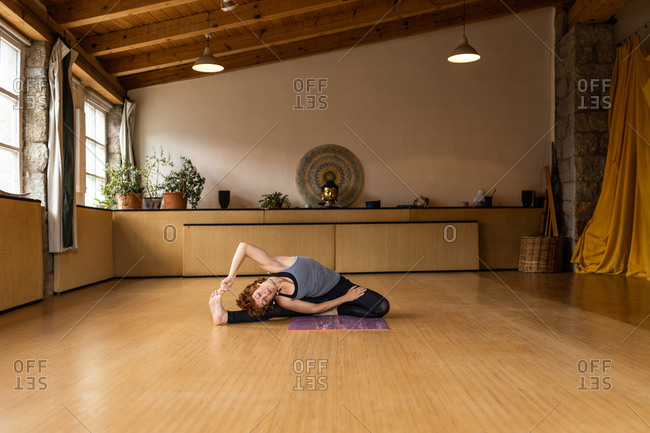 Female in sportswear sitting in revolved seated angle while practicing Shakti yoga alone in light studio with wooden interior in tropical resort
