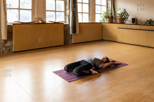Full body side view of flexible female in sportswear performing Extended Supine Hero pose during Shakti yoga practice in spacious studio with wooden interior